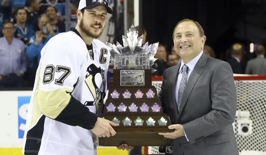 FILE - In this Sunday, June 12, 2016 file photo, Pittsburgh Penguins center Sidney Crosby (87) poses for photos with commissioner Gary Bettman as he accepts the Conn Smythe Trophy after Game 6 of the NHL hockey Stanley Cup Finals between the San Jose Sharks and the Penguins in San Jose, Calif. The Penguins won 3-1 to win the series 4-2. A huge turnout is expected in downtown Pittsburgh for the 2016 Stanley Cup champion Pittsburgh Penguins victory parade on Wednesday, June 15, 2016. (Bruce Bennett/Getty Images via AP, Pool, File)