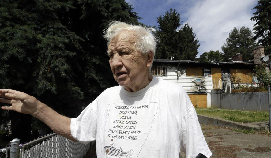 "Bob Wheeler, who has lived in the same house since he was 14 years old, stands outside a neighboring fire-damaged, abandoned and boarded-up house in Portland, Ore., Tuesday, June 14, 2016. City officials in this booming Pacific Northwest metropolis have developed a plan to foreclose on so-called ""zombie homes"" for first time in 50 years as Portland grapples with a swelling population and skyrocketing home costs that threaten to lock new homeowners out of the market. (AP Photo/Don Ryan)"