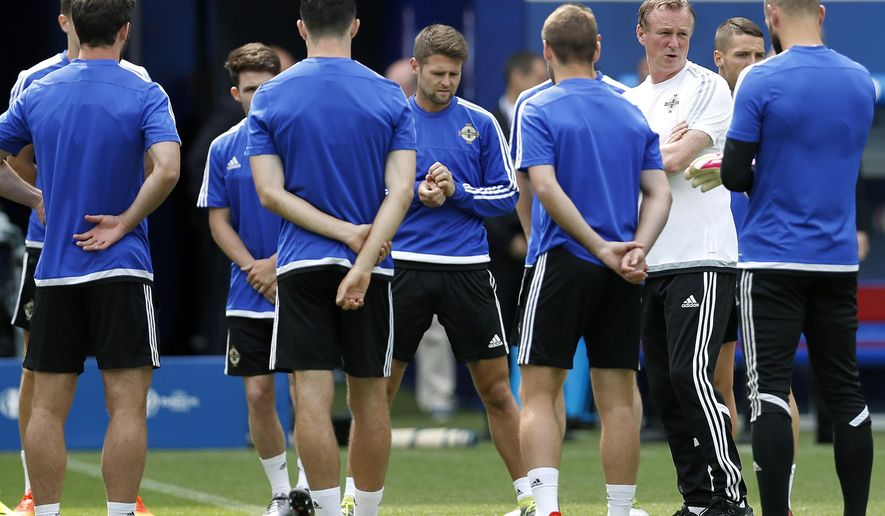 Northern Ireland coach Michael O'Neill, white jersey right, talks to the players during a training session at the Grand Stade in Decines-Charpieu, near Lyon, France, Wednesday, June 15, 2016. Northern Ireland will face Ukraine in a Euro 2016 Group C soccer match in Lyon on Thursday, June 16, 2016. (AP Photo/Michael Sohn)