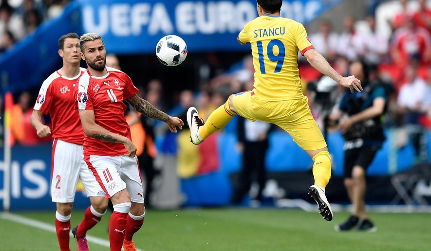 Romania's Bogdan Stancu, right, intercepts the ball in front of Switzerland's Valon Behrami during the Euro 2016 Group A soccer match between Romania and Switzerland at the Parc des Princes stadium in Paris, France, Wednesday, June 15, 2016. (AP Photo/Martin Meissner)