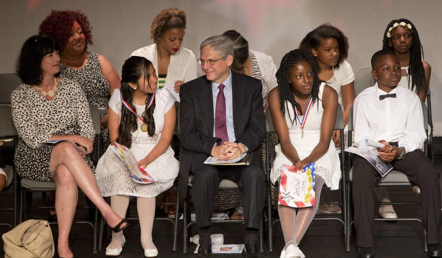 Merrick Garland,  President Barack Obama's choice to fill the Supreme Court vacancy,  center, congratulates Jenifer Morales-Garcia, left, after Morales-Garcia and Vernell Garvin, right, both fifth graders who Garland tutors, were awarded medals for math during the graduation ceremony for J.O. Wilson Elementary School, Wednesday, June 15, 2015, at the Atlas Performing Arts Center in Washington. Garland has tutored students at the school over the past 18 years. (AP Photo/Jacquelyn Martin)