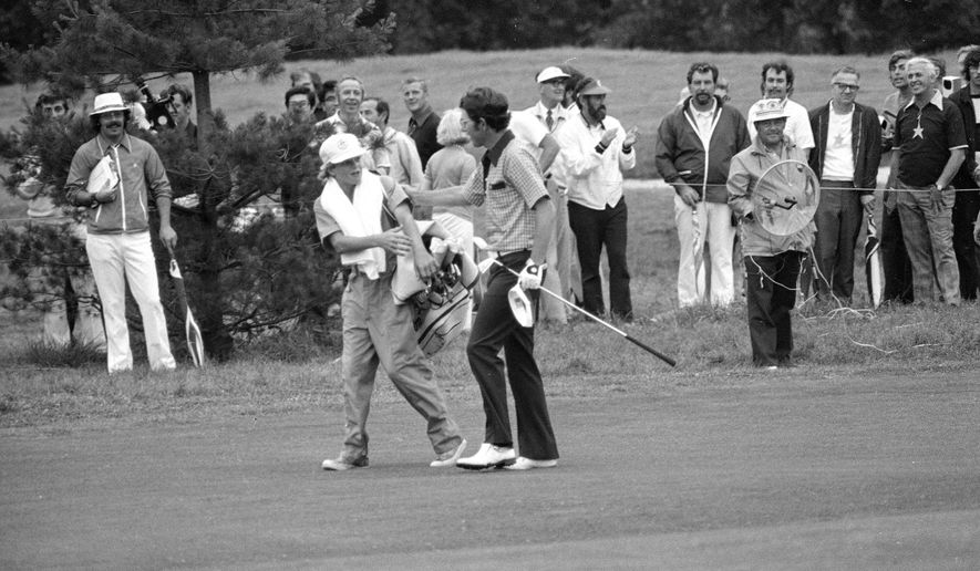 FILE - In this June 16, 1974, file photo, Peter McGarey, 16, of Scottsdale, Ariz., reaches to offer congratulations to Hale Irwin after the latter's fairway shot on the 18th reached the green and prior to Irwin's winning the U.S. Open golf championship in Mamaroneck, N.Y. Irwin closed with a 73 to capture the first of his three U.S. Open. Irwin won at 7-over 287. There has not been a higher winning score in relation to par at any major since then. (AP Photo/File)