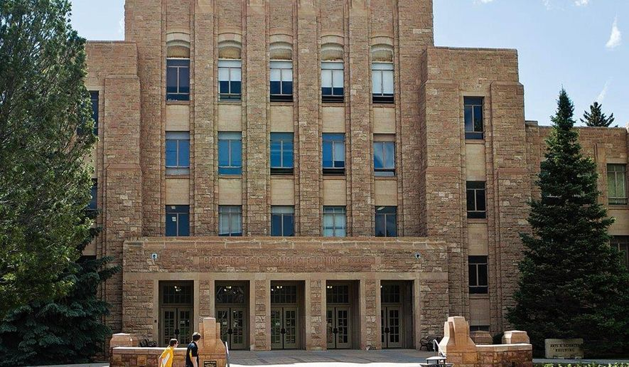 Two people walk on the University of Wyoming campus on Tuesday, June 14, 2016. The state's only public four-year university is having to find more than $40 million in savings over the next two years because of cuts in state aid caused by the drop in revenue from Wyoming's coal, oil and natural gas industry. The UW Board of Trustees was meeting Wednesday to address the cuts. (Shannon Broderick/Laramie Boomerang via AP)