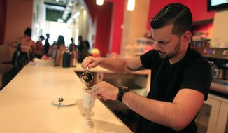 Walter Martin as he prepares a coffee in his coffee shop in the colonial district of Old San Juan, Puerto Rico, in this Sunday, Aug. 2, 2015, file photo. The World Health Organization's research arm has downgraded its classification of coffee as a possible carcinogen, declaring there isn't enough proof to show a link to cancer. (AP Photo/Ricardo Arduengo, File)