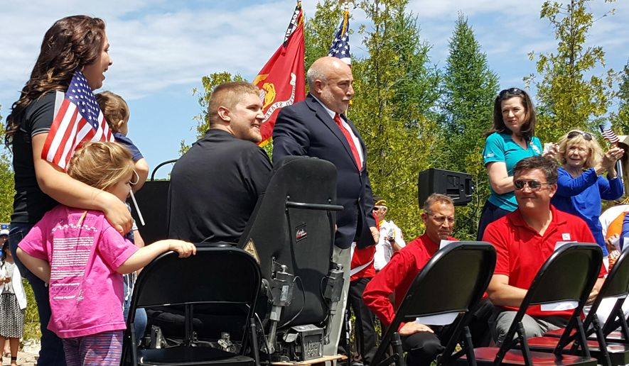 In this June 14, 2016 photo, from left, Ashley Eberle, her two children Halle and Landis, veteran Ben Eberle, and John Hodge of the Tunnel to Towers Foundation react to the unveiling of the Eberle's new smart home in Alpena, Mich. Army Staff Sgt. Eberle lost his legs and an arm after being struck by an improvised explosive device while serving in Afghanistan in 2011. The Stephen Siller Tunnel to Towers Foundation sponsored the home which is wheelchair-accessible and had electronic features that easier to use for Eberle. (Jason Ogden/Alpena News via AP)
