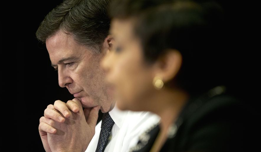 FBI Director James Comey listens at left as Attorney General Loretta Lynch speaks during their sit-down meeting with members of the media at Justice Department headquarters in Washington on Nov. 19, 2015, to discuss the U.S. government's ongoing counterterrorism efforts. (Associated Press) **FILE**