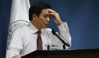 Philippine Foreign Affairs spokesperson Charles Jose touches his forehead as he answers questions from reporters in suburban Pasay, south of Manila, Philippines on Thursday, June 16, 2016. (AP Photo/Aaron Favila)