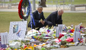President Barack Obama and Vice President Joe Biden visit a memorial to the victims of the Pulse nightclub shooting, Thursday, June 16, 2016 in Orlando, Fla. Offering sympathy but no easy answers, Obama came to Orlando to try to console those mourning the deadliest shooting in modern U.S history. (AP Photo/Pablo Martinez Monsivais)