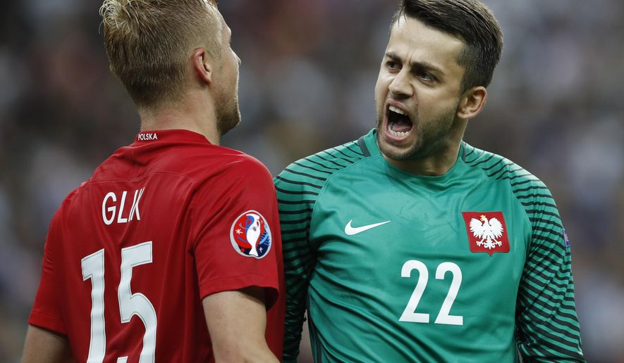 Poland goalkeeper Lukasz Fabianski, right, and Poland's Kamil Glik, celebrate at the end of the Euro 2016 Group C soccer match between Germany and Poland at the Stade de France in Saint-Denis, north of Paris, France, Thursday, June 16, 2016. The match ended in a 0-0 draw. (AP Photo/Christophe Ena)