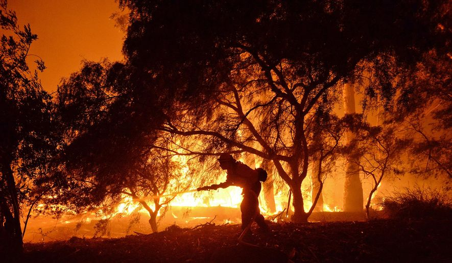 In this photo provided by the Santa Barbara County Fire Department, a firefighter knocks down flames as they approach a ranch near the Las Flores Canyon area west of Goleta, Calif., in the early morning hours of Thursday, June 16, 2016. The wildfire burning in rugged coastal canyons west of Santa Barbara is growing as it feeds on vegetation that hasn't burned in 70 years. (Mike Eliason/Santa Barbara County Fire Department via AP)