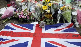A Union flag is placed in front of floral tributes in Birstall, northern England, for Jo Cox, the 41-year-old British Member of Parliament shot to death in northern England, Friday June 17, 2016. The mother of two young children was shot to death Thursday afternoon in her constituency near Leeds. A 52-year-old man has been arrested but has not been charged.  (Danny Lawson/PA via AP) UNITED KINGDOM OUT NO SALES NO ARCHIVE