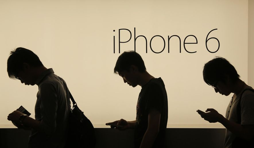 In this Friday, Sept. 19, 2014, file photo, people wait to buy the new Apple iPhone 6 and 6 Plus devices outside an Apple store in Hong Kong. (AP Photo/Vincent Yu, File)