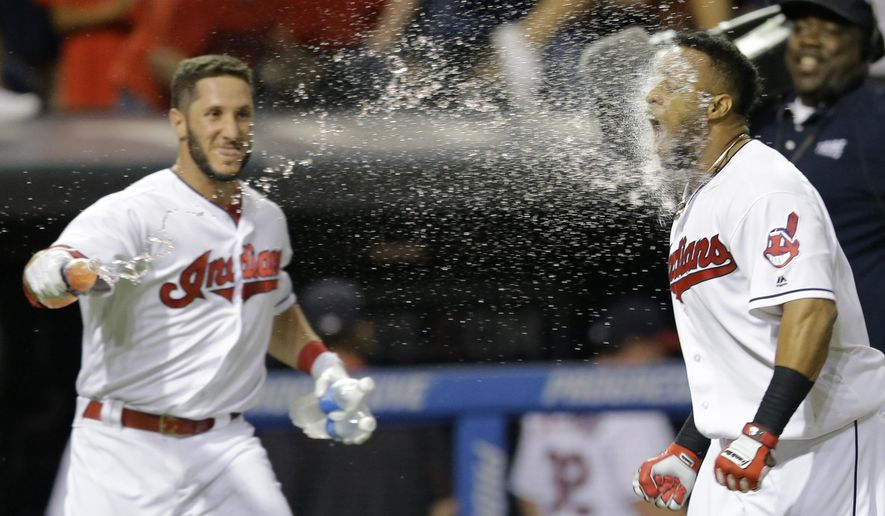 Cleveland Indians' Yan Gomes, left, throws water at Carlos Santana after Santana hit the game-winning solo home run off Chicago White Sox relief pitcher Nate Jones during the ninth inning of a baseball game, Friday, June 17, 2016, in Cleveland. The Indians won 3-2. (AP Photo/Tony Dejak)