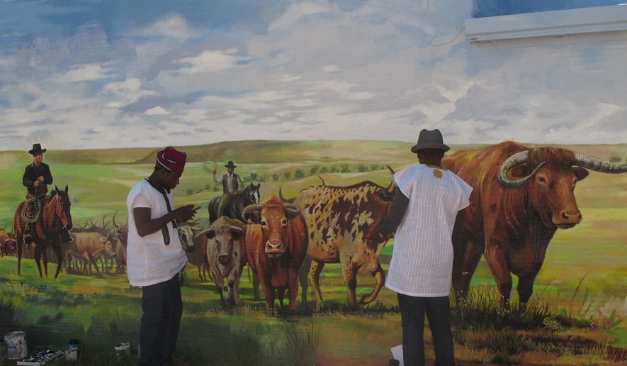 In this June 1, 2016 photo, Dotun Popoola, left, and Jonathan Imafidor work on the mural they've painted in what is becoming Boss Cowman Square in Lemmon, S.D. (Lauren Donovan /The Bismarck Tribune via AP) MANDATORY CREDIT