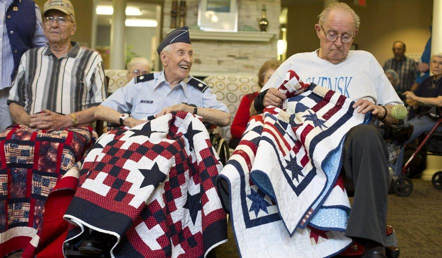 ADVANCE FOR USE SUNDAY, JUNE 19 - In this photo taken Thursday, June 9, 2016, Jack Joslyn, 93, center, smiles during the presentation of Quilts of Valor at The Sanctuary of Oaks in Muskegon, Mich. The quilts were made by the Old Jail Quilters from Big Rapids, which is a local chapter of the larger Quilts of Valor Foundation. (Emily Brouwer/Muskegon Chronicle via AP) ALL LOCAL TELEVISION OUT; LOCAL TELEVISION INTERNET OUT; MANDATORY CREDIT