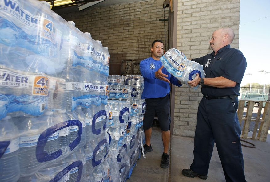 Glendale Fire Department firefighter Chris Greene, right, gets a case of water from service worker Edi Marroquin, left, from the dozens of cases of water at the Glendale Fire Department Resource Center as they prepare for the record-setting heat predicted for the weekend Thursday, June 16, 2016, in Glendale, Ariz. (AP Photo/Ross D. Franklin)