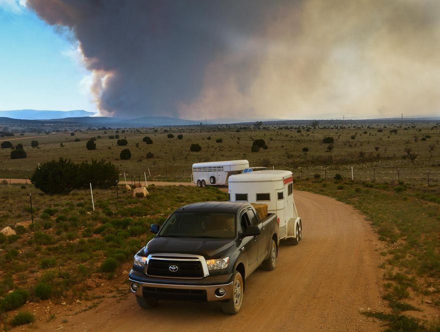 East mountain residents evacuate their homes as the Dog Head Fire burns on Thursday, June 16, 2016 in Albuquerque, N.M. Firefighters struggled Thursday to make progress against a fast-moving wildfire in central New Mexico as it consumed tinder dry forest, sent up a towering plume of smoke that could be seen for miles, and forced more residents from their homes. (Greg Sorber/The Albuquerque Journal via AP) MANDATORY CREDIT