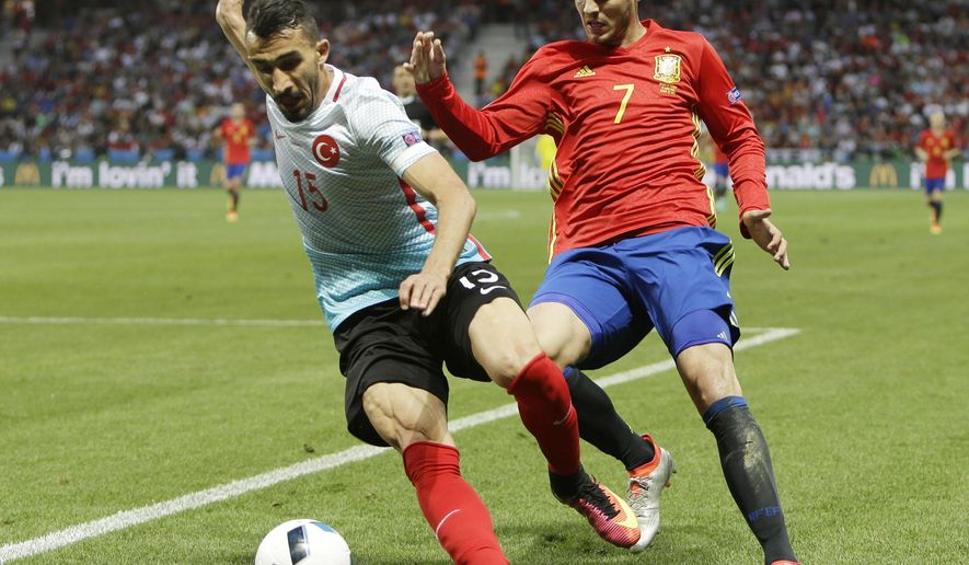 Spain's Alvaro Morata, right, challenges Turkey's Mehmet Topal during the Euro 2016 Group D soccer match between Spain and Turkey at the Allianz Riviera stadium in Nice, France, Friday, June 17, 2016. (AP Photo/Claude Paris)