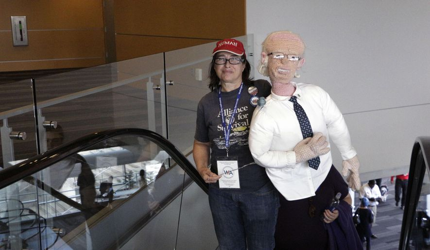 Donna Burdick of Everett carries a crochet Bernie Sanders as she arrives at the Washington Democratic Convention, Friday, June 17, 2016, in Tacoma, Wash. State Democrats are meeting to pass a party platform and finish electing delegates to the national convention this summer. (AP Photo/Rachel La Corte)