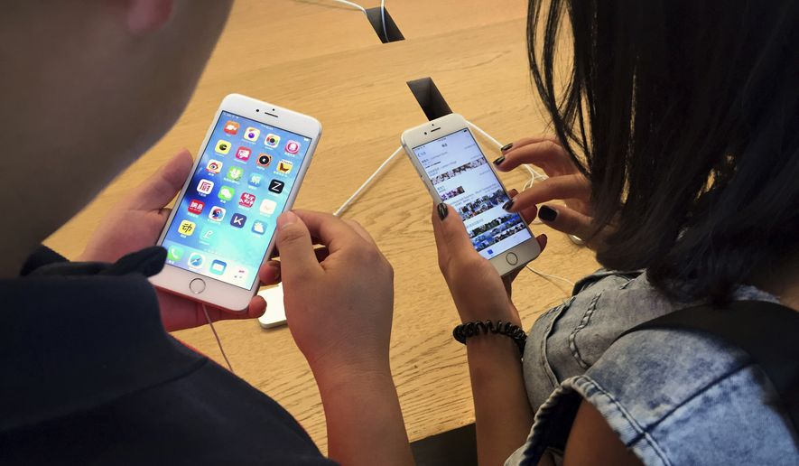 Customers try out Apple iPhone 6S models on display at an Apple Store in Beijing, Saturday, June 18, 2016. (AP Photo/Mark Schiefelbein) **FILE**