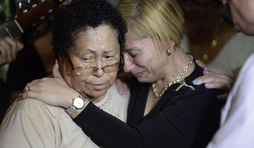 Aide Cintron, left, and Lety Padro, grandmother and aunt of Angel Candelario Padro, mourn at his wake in Guanica, Puerto Rico, Thursday, June 16, 2016. Angel Candelario Padro was one of the 23 Puerto Ricans that died at the hands of a gunman at a nightclub in Orlando, Florida. (AP Photo/Carlos Giusti)