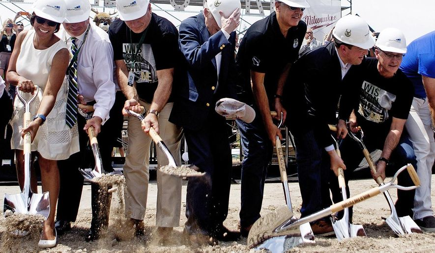 A ceremonial shovel flies out of former Senator Herb Kohl's, center with hand on hard hat,  hands during the groundbreaking ceremony at the new Milwaukee Bucks Arena groundbreaking ceremony on North 4th and Juneau Street in Milwaukee, Wis., on Saturday, June 18, 2016. (Calvin Mattheis/Milwaukee Journal-Sentinel via AP) MANDATORY CREDIT