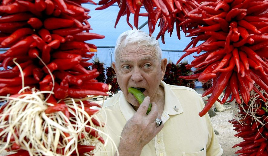 FILE - In this Aug. 30, 2008 file photo, framed by ristras, John Trewitt bites into a pod of fresh Hatch green chile, at the Hatch Chile Festival in Hatch, N.M. A federal appeals court is siding with an association of green chile growers in the Hatch Valley of southern New Mexico in a dispute over what food can be fairly labeled with the renowned Hatch name. The U.S. 10th Circuit Court of Appeals on Friday, June 17, 2016, ruled in favor of the Hatch Chile Association and allied Albuquerque food distributor El Encanto in their efforts to subpoena records that may indicate whether a rival's products contain purely Hatch-grown chile as marketing suggests. (Norm Dettlaff/The Las Cruces Sun-News via AP, File) MANDATORY CREDIT