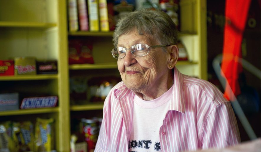 ADVANCE FOR WEEKEND EDITIONS JUNE 18-19 - In this June 9, 2016 photo, owner of the Fremont Store Martha Johnson looks outside during a tour of the store in Winona County, Minn. Martha Johnson has owned and run the store with family and community assistance since 2004 after her son Donnie died. She'll celebrate the store's 160th anniversary Saturday, June 18, 2016 with a party that's expected to draw neighbors, long-time regulars, and those simply curious to meet the character responsible for keeping up what is likely Minnesota's oldest continuously run grocery store. (Jacob Striker/The Winona Daily News via AP) MANDATORY CREDIT