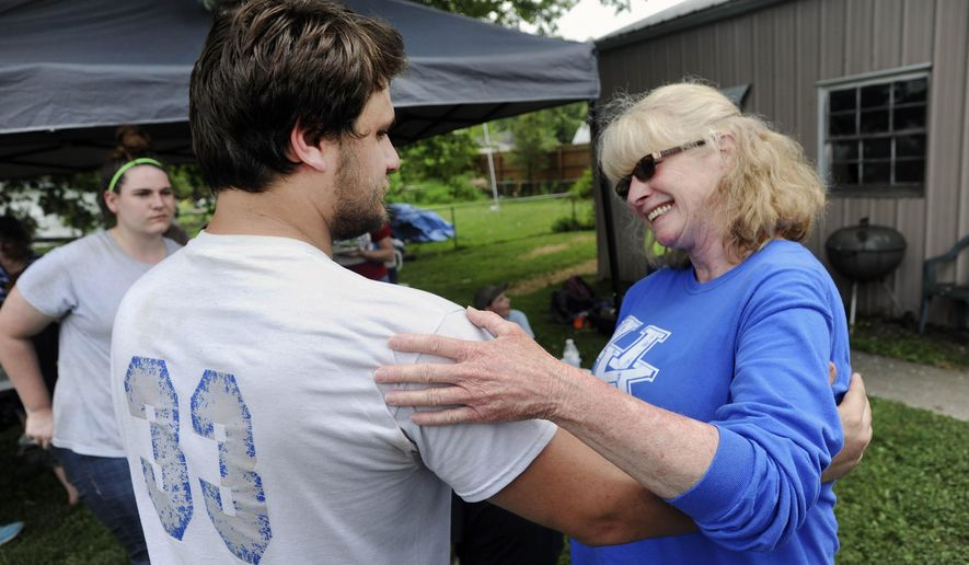 World Changers member Austin Weathers of Red Bay, Ala, left, gets thanked by home owner, Donna Stinnett, right, as they take a break from repairing her roof while in Owensboro, Ky., on Wednesday, June 15, 2016. The World Changers started working on Monday in Owensboro repairing roofs, painting, and doing yard work for 18 selected homes. (Alan Warren/Messenger-Inquirer via AP) MANDATORY CREDIT