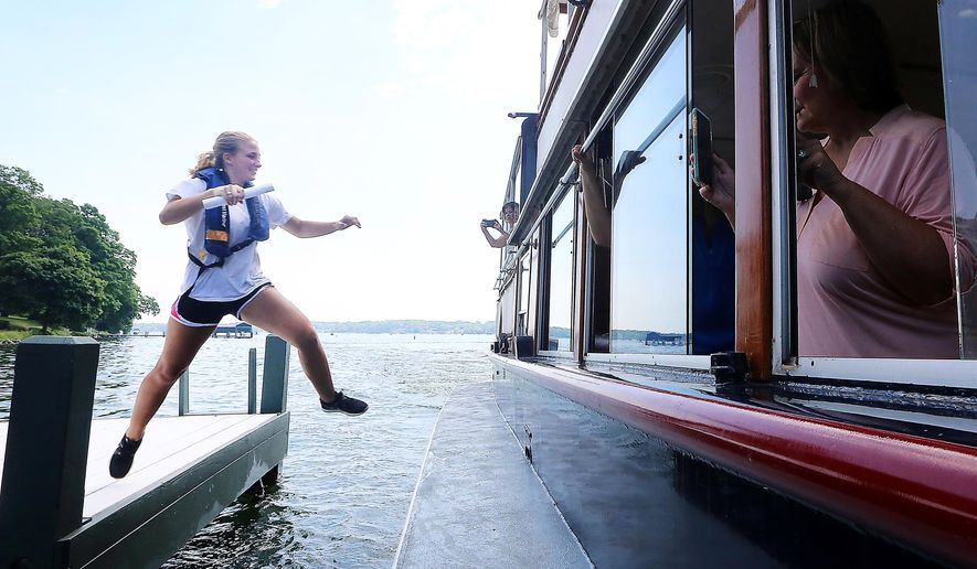 ADVANCE FOR MONDAY, JUNE 20, 2016- Joanie Williams leaps aboard U.S. mail boat The Walworth during an audition exercise for prospective mail jumpers hoping to work aboard the vessel on Lake Geneva in Lake Geneva, Wis. Friday, June 10, 2016. (John Hart/Wisconsin State Journal via AP) MANDATORY CREDIT