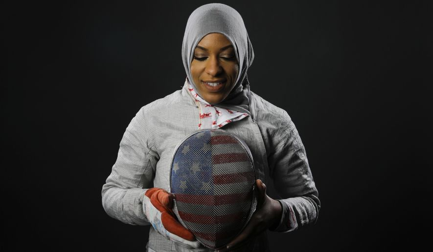 FILE - In this March 8, 2016, file photo, Fencer Ibtihaj Muhammad poses for photos at the 2016 Olympic Team USA media summit in Beverly Hills, Calif. Muhammad will make history at the Rio Games by becoming the first American athlete to wear a hijab _ a Muslim head scarf _ while competing in the Olympics. (AP Photo/Jae C. Hong, File)