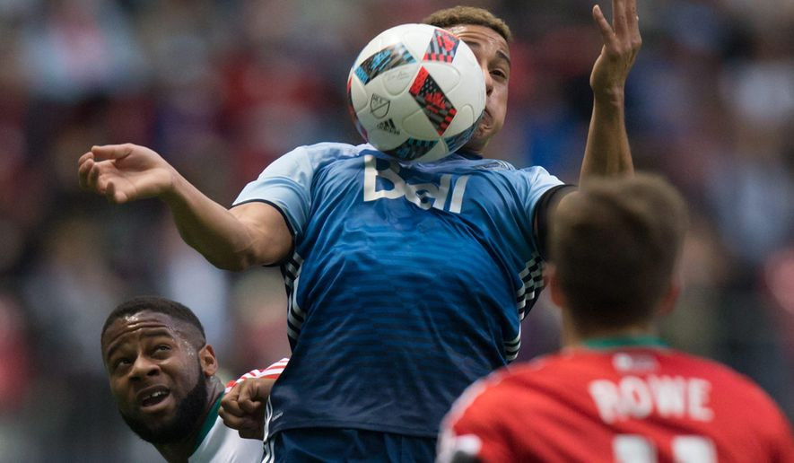 Vancouver Whitecaps' Erik Hurtado, center, traps the ball with his chest as New England Revolution's Andrew Farrell, left, watches during first-half MLS soccer game action in Vancouver, British Columbia, on Saturday, June 18, 2016. (Darryl Dyck/The Canadian Press via AP) MANDATORY CREDIT
