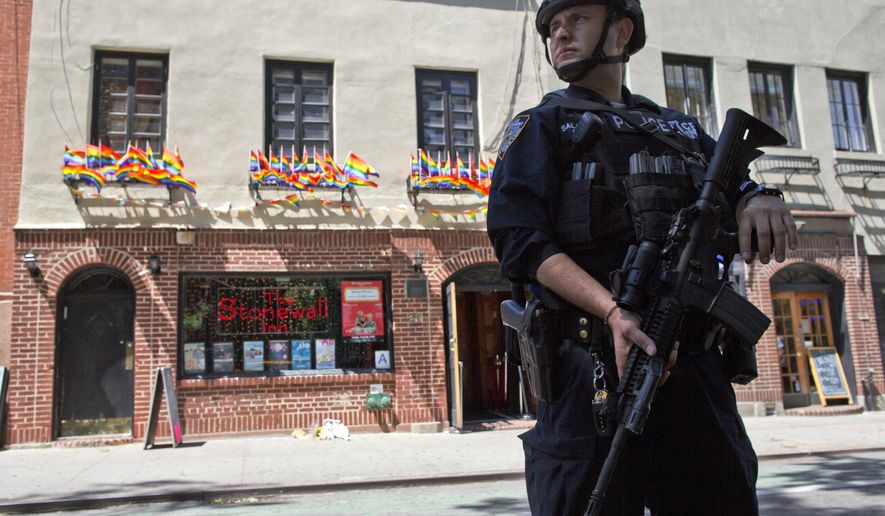 FILE - In this June 12, 2016 file photo, an armed police officer stands guard outside the Stonewall Inn, in New York. Decades ago, an early morning raid at the Stonewall Inn in New York sparked violent protests among gay patrons who fought back after police burst in and tried to arrest them for daring to drink and dance with members of the same sex. Nearly 50 years later, officers armed with assault rifles stand guard outside the historic bar, protecting patrons after a gunman in Florida massacred a gay nightclub and spread fear of more attacks. (AP Photo/Mary Altaffer, File)
