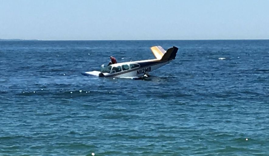 In this photo provided by Larry Schwartz, a man gets out of a plane after it crashed into the water off the coast of Westerly, R.I., Saturday, June 18, 2016. Officers were on the scene of the crash Saturday afternoon near the small beachfront community of Weekapaug. (Courtesy of Larry Schwartz via AP)