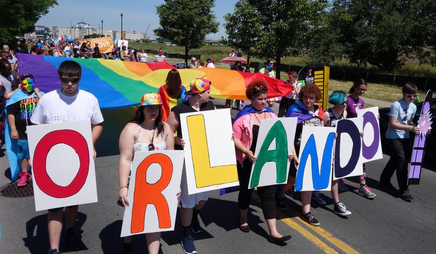 A youth group from ACR Health carry letters to commemorate the mass shooting in Orlando, Fla., during the Gay Pride Parade in Syracuse, N.Y., Saturday, June 18, 2016. Thousands of people have attended a lesbian, gay, bisexual and transgender pride parade and festival in upstate New York, less than a week after a deadly attack at a gay nightclub in Orlando. (Michael Greenlar/The Syracuse Newspapers via AP) MANDATORY CREDIT