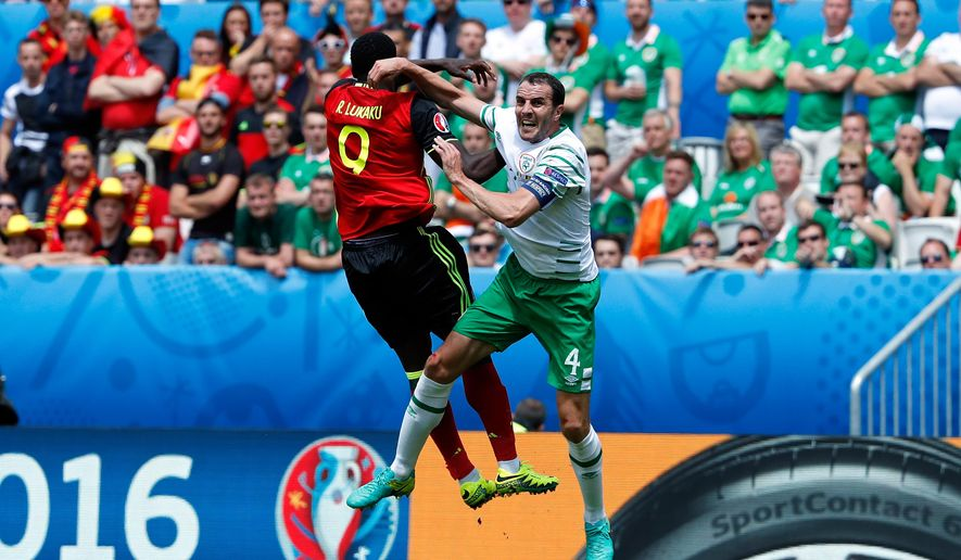 Belgium's Romelu Lukaku, left, jumps for the ball with Ireland's John O'Shea during the Euro 2016 Group E soccer match between Belgium and Ireland at the Nouveau Stade in Bordeaux, France, Saturday, June 18, 2016. (AP Photo/Hassan Ammar)