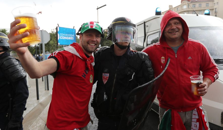 Hungarian fans pose for a photograph with a French policeman before the Euro 2016 Group F soccer match between Iceland and Hungary at the Velodrome stadiumin Marseille, France, Saturday, June 18, 2016. (AP Photo/Claude Paris)