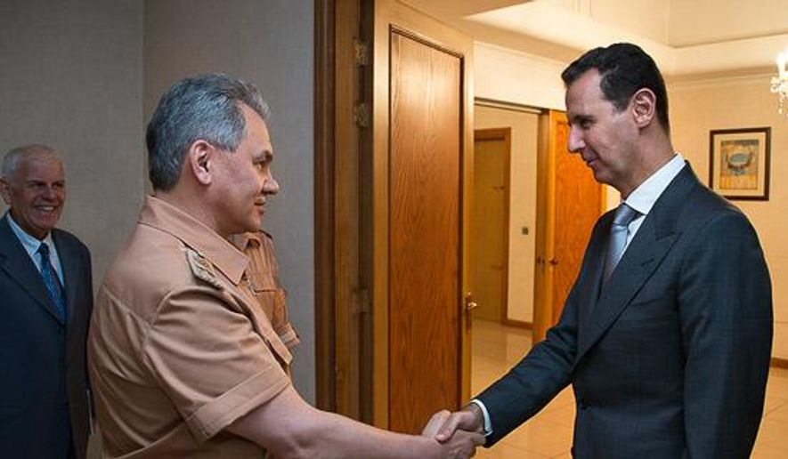 Syrian President Bashar Assad shakes hands with Russian Defense Minister Sergei Shoigu in Damascus, Syria, Saturday, June 18, 2016. Russia's defense minister visited Syria on Saturday to meet the country's leader and inspect the Russian air base there, a high-profile trip intended to underline Moscow's role in the region. (Vadim Savitsky/ Russian Defense Ministry Press Service pool photo via AP)