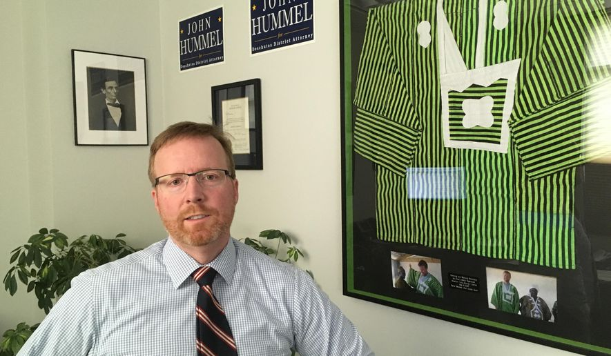 Deschutes County District Attorney John Hummel stands in his Bend, Ore., office Wednesday, May 15, 2016, next to a gown he received in 2009 while working for the Carter Center in Liberia. Hummel, who is examining about 1,500 convictions after a state police forensics lab technician allegedly tampered with evidence, says his experiences in the West African country helps guide him. (AP Photo/Andrew Selsky)