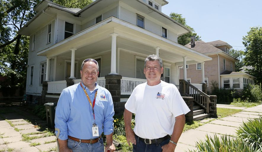 ADVANCE FOR USE SUNDAY, JUNE 19 - In this photo taken Wednesday, June 15, 2015, Veteran Affairs executive director Kevin Dill, left, and Tim Combs director of Americans for Independent Living, pose in front of a home in Waterloo, Iowa. Veterans advocates received a welcome gift when an anonymous donor offered a home on Waterloo's east side that can soon serve as a veterans homeless shelter for the community.  (Brandon Pollock/The Courier via AP) MANDATORY CREDIT