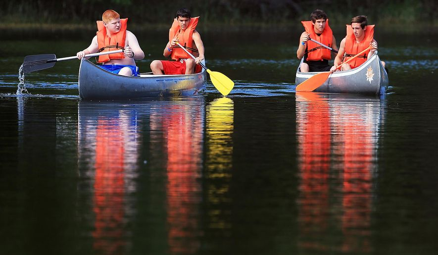 ADVANCE FOR SUNDAY JUNE 19 AND THEREAFTER - Working on their canoeing skills, from left, Troop 103 members Cole Ewoldt and Isaiah Magana of Cairo paddle their canoe, while Troop 164's  Dakota Solway of Sutton paddles with staff member Austin Seamann, on Tuesday, June 14, 2016, while participating in a Boy Scouts camp at Camp Augustine south of Grand Island, Neb. The camp offers a choice of 45 merit badges, and participants usually average between one and eight badges during the camp. (Barrett Stinson/The Grand Island Independent via AP)