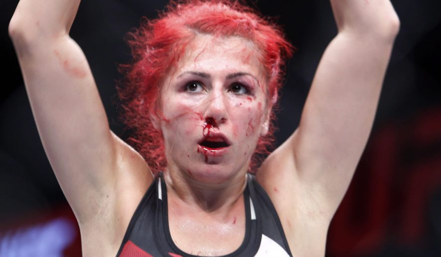 Randa Markos, of Canada, raises her arms after winning her strawweight bout against Jocelyn Jones-Lybarger at UFC Fight Night 89 on Saturday, June 18, 2016 in Ottawa, Ontario. (Fred Chartrand/The Canadian Press via AP)