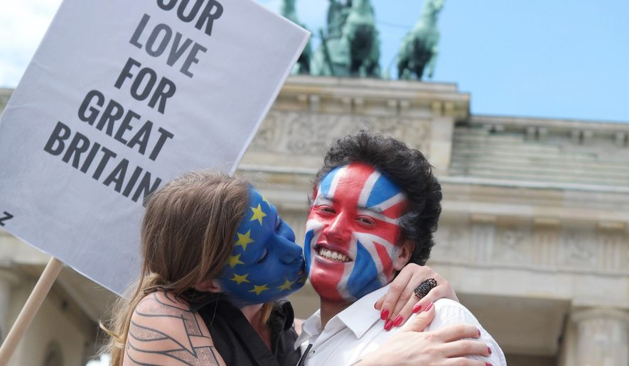 """LED IN: A young couple  with  faces paint in European, left,  and British  colors, pose with a sign """"Our Love For Great Britain"""" during a Kiss Marathon event   at Brandenburg Gate in Berlin, Germany, Sunday June 19,  2016 to support the ' Remain'  voters in Britain's referendum. The campaign in the referendum over Britain's future in the European Union is about to resume full throttle after being on hold due to the killing of a popular lawmaker.  British voters head to the polls on Thursday to decide if the country should stay in the European Union or leave it.  (Joerg Carstensen/dpa via AP) (Associated Press)"""