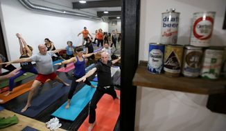 In this Thursday, Dec. 3, 2015, Greg Harris, right, practices yoga at the Platfrom Beer Co, in Cleveland. Craft breweries are partnering up with yoga studios around the country as more breweries are hosting classes to attract a new crowd to the bars and yoga studios are using the beer to get more men to try yoga. (AP Photo/Tony Dejak) **FILE**