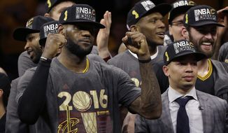 Cleveland Cavaliers forward LeBron James, left, celebrates with head coach Tyronn Lue, right, and teammates after Game 7 of basketball's NBA Finals against the Golden State Warriors in Oakland, Calif., Sunday, June 19, 2016. The Cavaliers won 93-89. (AP Photo/Marcio Jose Sanchez)
