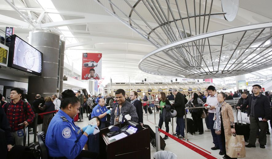 A TSA officer (left) checks a passenger's ticket, boarding pass and passport as part of security screening at John F. Kennedy International Airport in New York on Oct. 30, 2014. (Associated Press) **FILE**