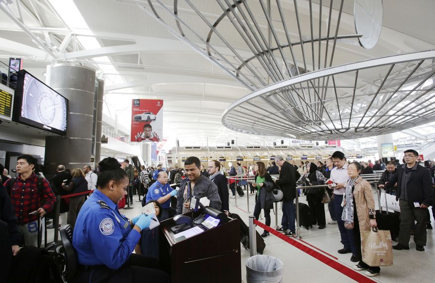 A TSA officer (left) checks a passenger's ticket, boarding pass and passport as part of security screening at John F. Kennedy International Airport in New York on Oct. 30, 2014. (Associated Press) **FILE**