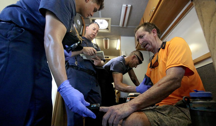 Jeff Mayhew, right, with the Southern Arizona Rescue Association, gets his vitals checked by members of Rural/ Metro Fire Dept., north of Tucson, Ariz., Monday, June 20, 2016. Mayhew returned from the search for a missing hiker in the Ventana Canyon area. Several hikers have died over the weekend from heat-related problems. On Sunday three Germany men went hiking in the Ventana Canyon area of the Santa Catalina Mountains. One died, one is missing and the other is hospitalized, authorities said. (A.E. Araiza/Arizona Daily Star via AP) MANDATORY CREDIT