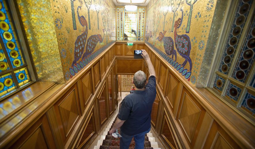 In this Saturday, June 11, 2016 picture a visitor takes pictures during a tour of Romanian communist dictator Nicolae Ceausescu's former family home, dubbed the Palace of Spring in Bucharest, Romania. More than 26 years after Nicolae and Elena Ceausescu were shot dead after a summary trial during the 1989 anti-communist revolt, fascination with the couple's opulent lifestyle remains, with thousands, Romanians and foreigners, visiting the Palace of Spring since it was transformed into a museum in March 2016.(AP Photo/Vadim Ghirda)
