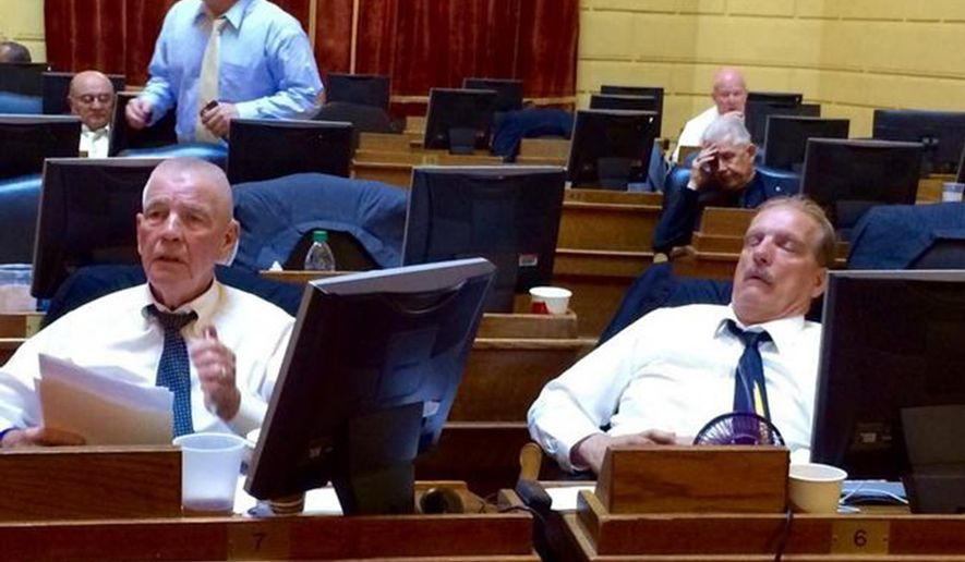 In this photo taken Saturday, June 18, 2016, Rep. James McLaughlin, D-Cumberland, left, follows the action on the floor of the House in the early morning while Rep. Robert Phillips, D-Woonsocket, dozes near the end of the Rhode Island General Assembly's marathon final day of the session. (Alisha Pina /Providence Journal via AP) NO SALES; MANDATORY CREDIT